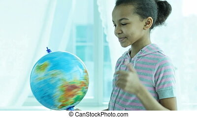 Spinning the globe - Cute African-American girl spinning the...