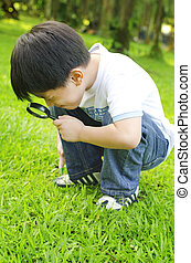 Discovering - Little boy exploring nature by magnifier