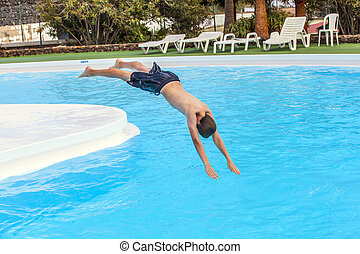 boy jumping in the blue pool - boy has fun jumping in the...