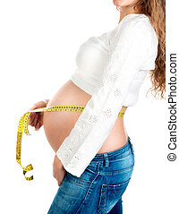 pregnant woman measures her stomach