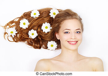 Beautiful girl with flowers in hair on a light background