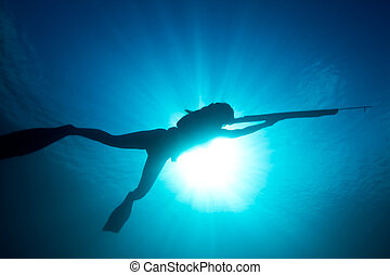 Tropical spearfishing - A young woman stalks her prey...