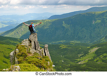 Woman in montains on rock with back pack with his arms...