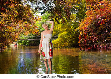 The girl with a bunch of flowers, standing in the river