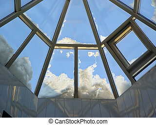 glass roof with lying on it snow on a background blue sky