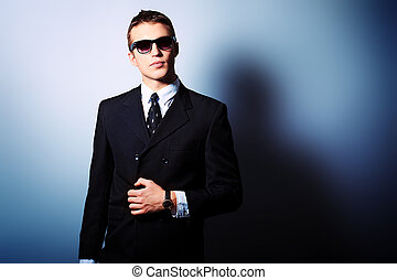 coat black - Portrait of a handsome young man in a suit....