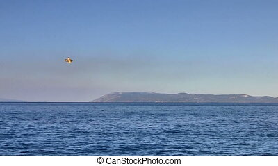 Yellow airplane flying over sea in Croatia