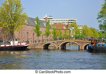 Beautiful river with ships, Hermitage and Amstel bridge in...