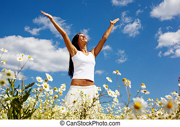 Sunny girl - Young woman holding hands high up while...