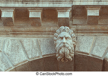 high relief - the stone head of the man with a twisted beard...