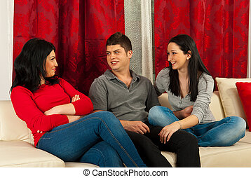 Friends having conversation on sofa - Three happy friends...