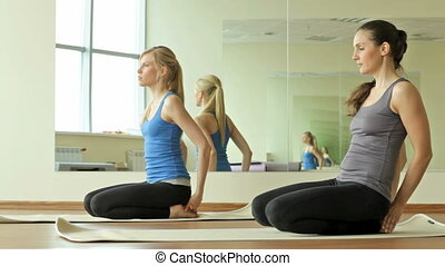Stretch and relax - Women in a gym performing yoga asanas...