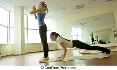 Complex shape - Young sportive women exercising, one of them...