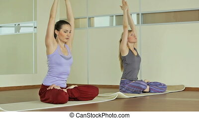 Lotus pose - Girls sitting in lotus pose, leaning forward to...