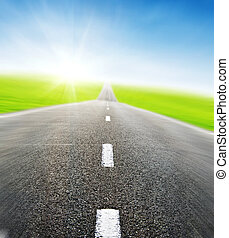 road over blue sky in motion - green field and road over...