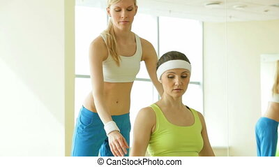 Developing biceps - Girl with dumbbells sitting on a fitness...
