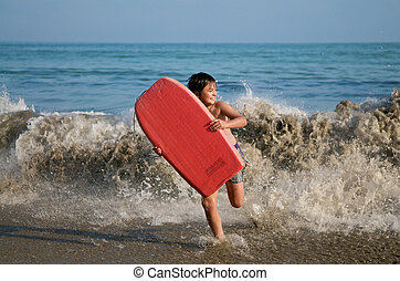 Boy running with surfing board - Boy running on the beach...