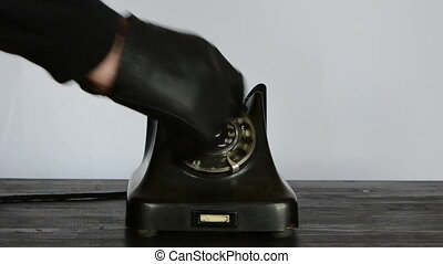 calling with antique phone - hand with black dermal glove...