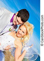 happy groom and bride on a sea coast