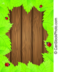 Wooden background with fresh green leaves.