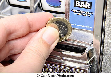 Slot machine : slot to introduce coins and finger holding...