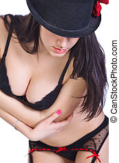 Sexy brunette in lingerie and hat, posing in the studio....