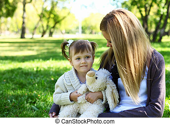 Little girl playing with mother in summer park