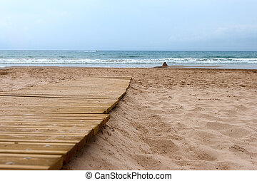 Wooden boardwalk on sand on the beach