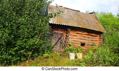 old obsolete russian bath-house in lush foliage