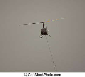 Helicoptor with a water bucket fighting fire