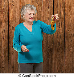 Senior woman holding a rotten banana against a wooden...