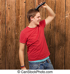 portrait of young man cutting his hair against a wooden wall...
