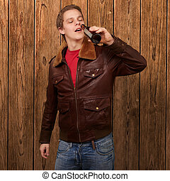 portrait of young man drinking beer against a wooden wall