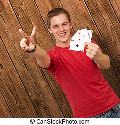 portrait of young man doing a victory gesture playing poker...