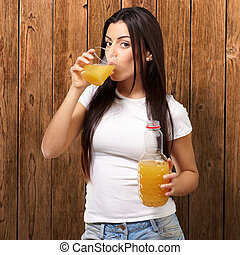 portrait of young girl drinking orange juice against a wooden wall