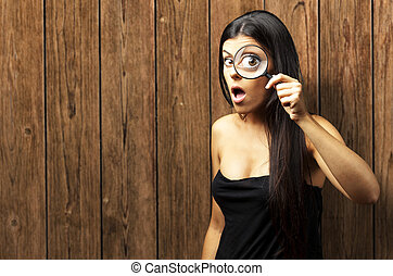 Young woman surprised looking through a magnifying glass...