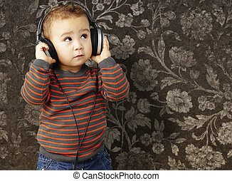 portrait of a handsome kid listening to music looking up against