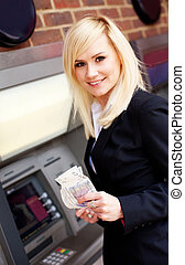 Woman with money at automatic teller