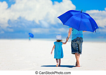 Father and daughter walking at beach - Father and daughter...