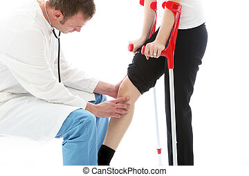 Orthopaedic surgeon examining woman's knee - Orthopaedic...