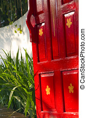Bright red wooden gate leading to a lush garden - Bright red...