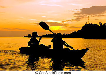 Silhouette of Two person kayaking in the sea at sunset in...