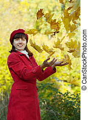 Girl throw up maple leaves - Girl in red coat throw up maple...