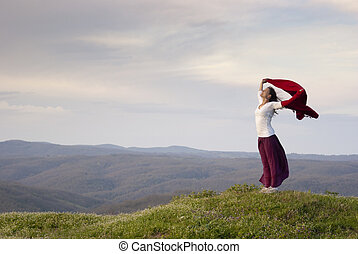 Freedom - Beautiful young woman standing on top of mountain...