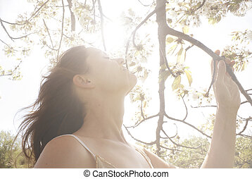 Blissful Light - Beautiful young woman smelling the blossom...