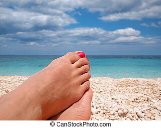 Lazy feet on the beach - Female feet with red polished nails...