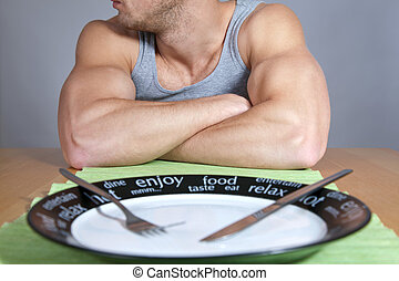 Muscular man with empty plate - Muscular man sitting at the...