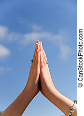 Praying hands - Hands praying in front of a blue sky