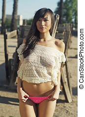 Beautiful Asian woman in bikini and baggy knit top