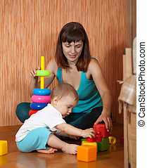 Baby girl plays with toy blocks